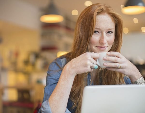 woman on laptop smiling drinking coffee