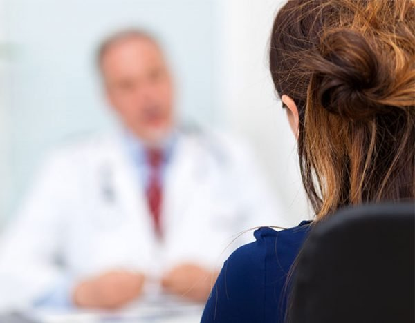 woman speaking to doctor GP