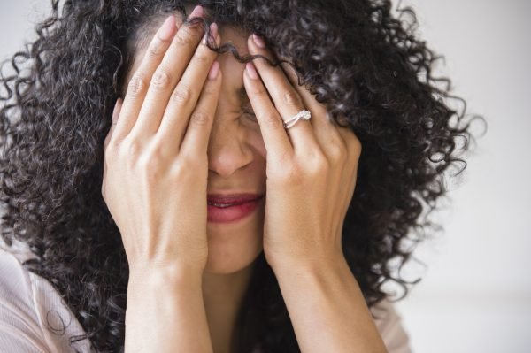 Mixed race woman with curly hair covering her face